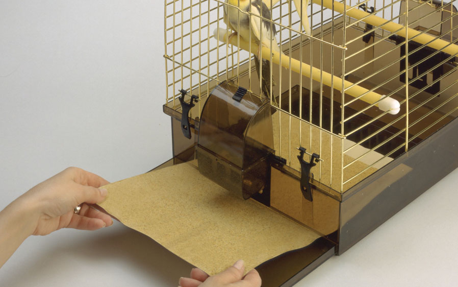 image illustrating hartz universal gravel paper being added to a bird cage